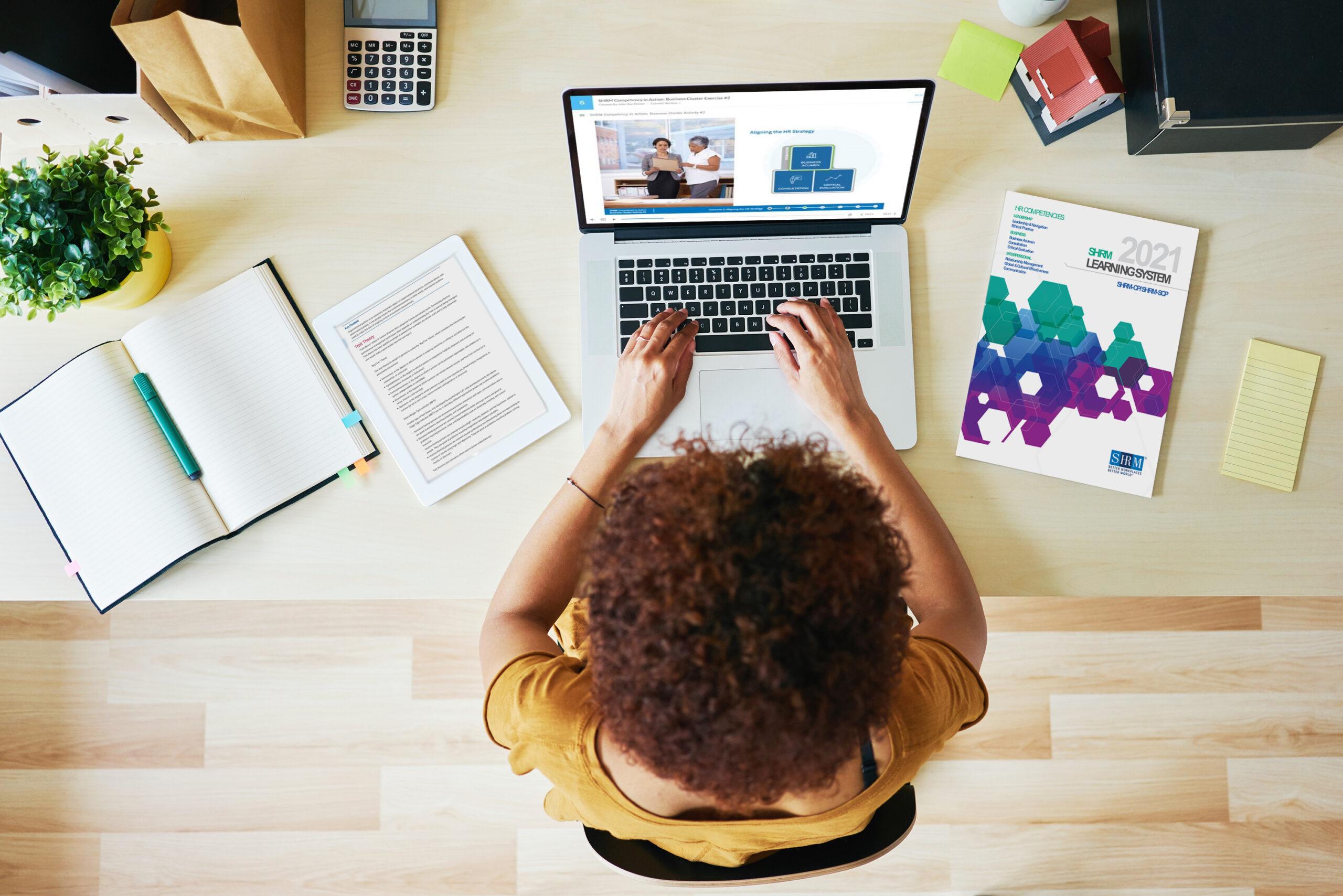 Woman using laptop next to SHRM textbook