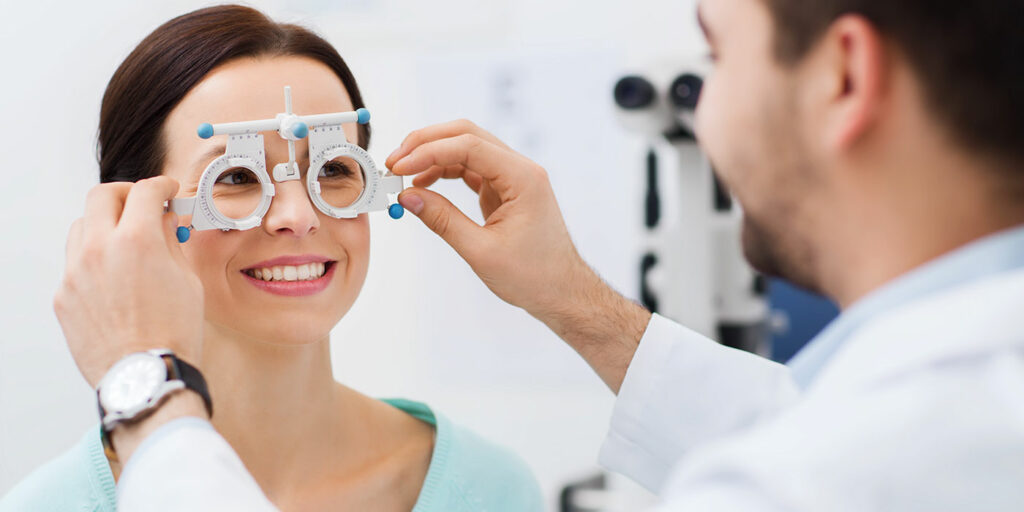 Optician measuring patient's eyes