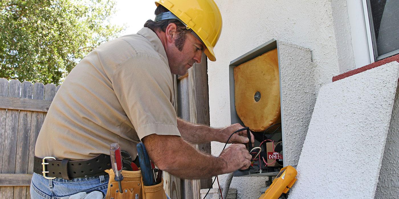 Man in safety hat repairing equipment